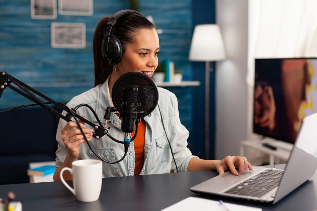 Woman podcaster speaking into the microphone with a computer in front of her wearing headphones